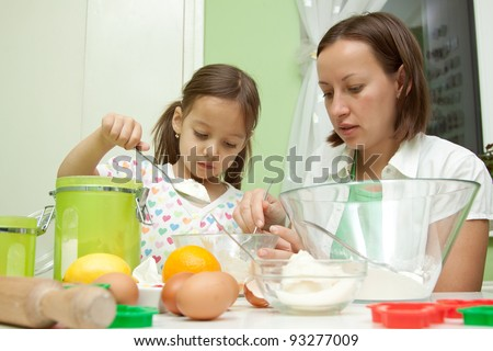 daughter helping her mother to bake a cake - stock photo