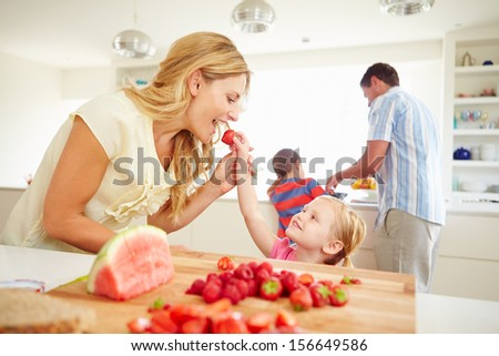 Daughter Helping Mother To Prepare Family Breakfast - stock photo