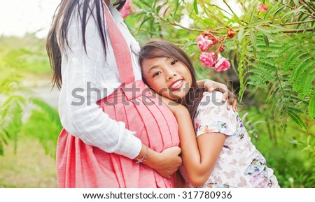 daughter hugging her mother's pregnant belly - stock photo