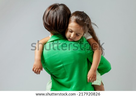 Daughter hugging her mother who is sitting on the floor - stock photo