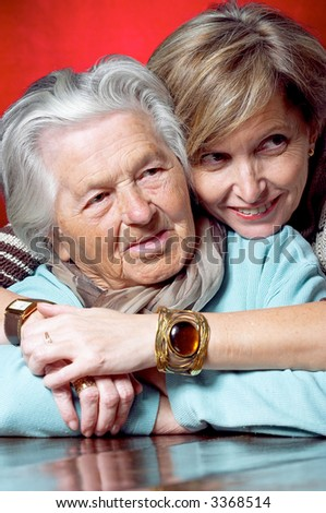 Daughter hugs her mother and they both are looking away