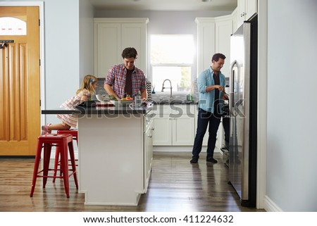 Daughter in kitchen watches her male parents prepare meal - stock photo