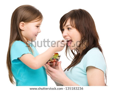 Daughter is feeding her mother with fruit salad, isolated over white