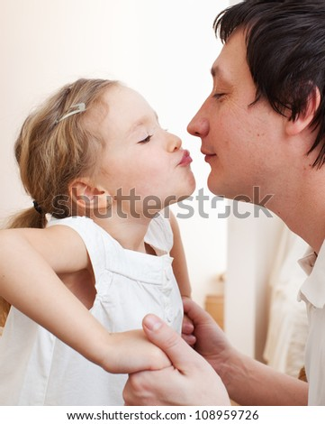 Daughter kissing her dad. Happy family