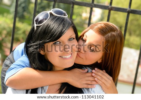 Daughter kissing her mother outdoors teen happy loving together leisure - stock photo