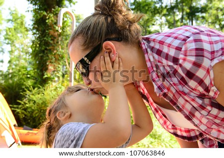 daughter kissing mom on camping trip - stock photo