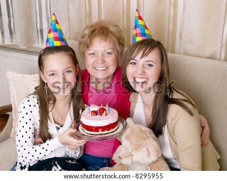 daughter, mother and grandmother with birthday cake - stock photo