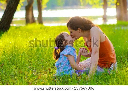 daughter mother kissing a baby woman sitting on the green grass nature summer sunset romance