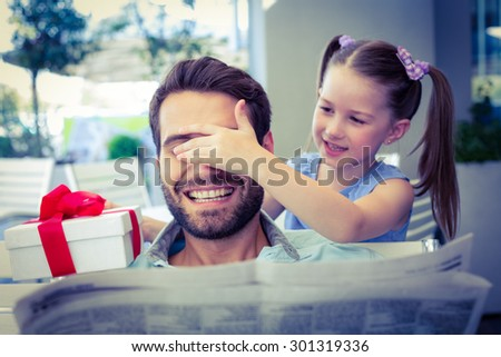 Daughter offering her present to her dad in the cafe - stock photo