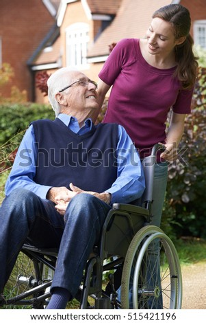 Daughter Pushing Senior Father In Wheelchair