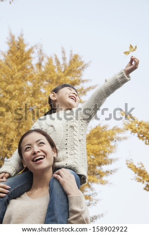 Daughter riding piggy-back on mother's shoulders and enjoying autumn leaves - stock photo