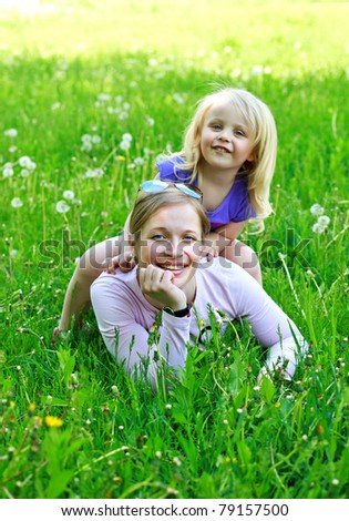 Daughter sits on mother on a grass outdoors smiling - stock photo