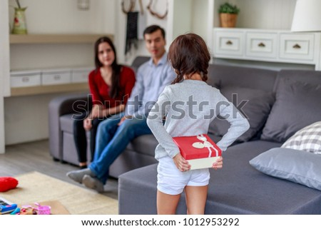 Daughter surprising father and mother with gift at home in the living room, happy family concept
