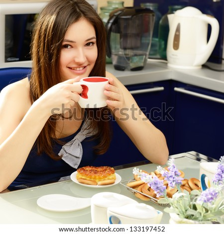Daughter teenager has breakfast and drinking tea in kitchen at home - stock photo
