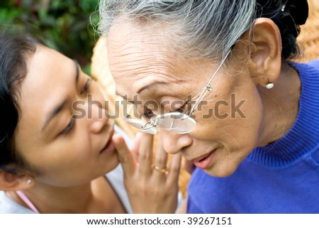 daughter whispering some serious issue to her old mother - stock photo