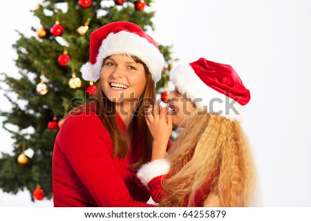 daughter whispers in her mothers ear - stock photo