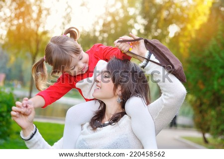 daughter with her mother in autumn. - stock photo