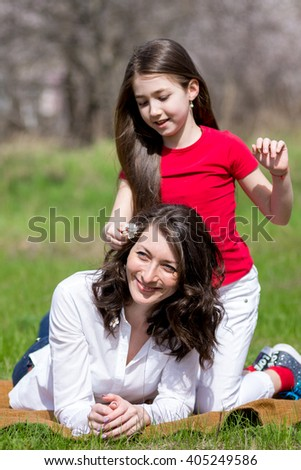 Daughter with the mother sitting on the grass in the spring, and communicate - stock photo