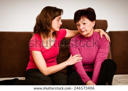 Daughter (young woman) comforts her depressed senior mother at home - stock photo