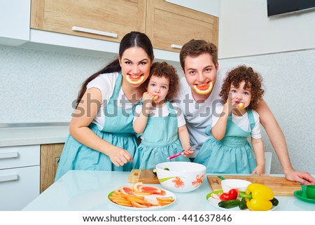 Daughters twins and parents in the kitchen cooking, smile and laugh, funny and happy. Portrait of young, happy family in the kitchen. A happy family. - stock photo
