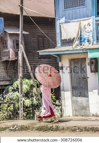 DAWEI, MYANMAR - FEBRUARY 15, 2015: A buddhist nun is walking along a street at Dawei, in the south of Myanmar. She is wearing a parasol. - stock photo