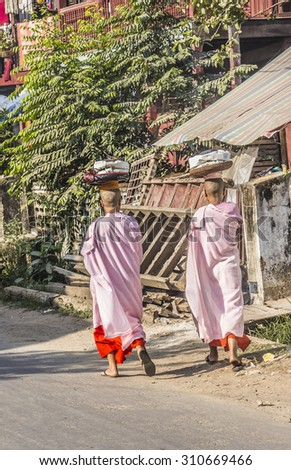 DAWEI, MYANMAR - FEBRUARY 16, 2015: Buddhist nuns are crossing a street  at Dawei, Myanmar. They are wearing parasols. - stock photo