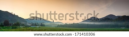Dawn breaking over misty mountains rustic villas and traditional farmland in Italy. - stock photo