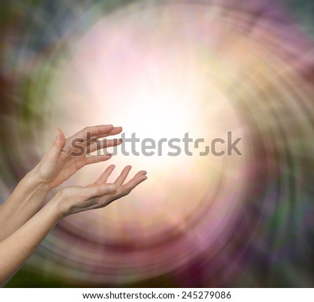 Dawn healing  - Pair of female hands reaching upwards into a gentle energy field vortex with plenty of copy space - stock photo