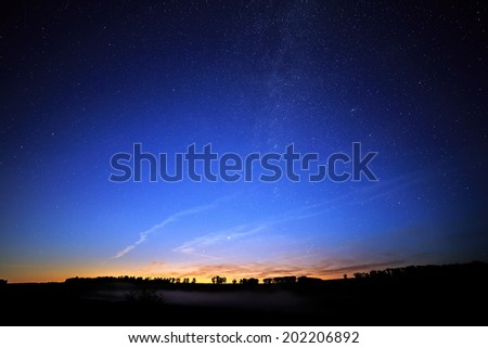 Dawn on a starry background sky and the Milky Way. - stock photo