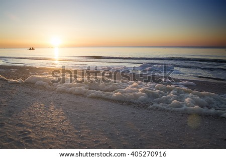 Dawn on the sea, sea foam on the shore, the fishermen on the boat - stock photo