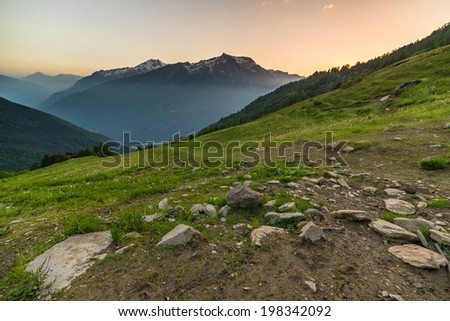 Dawn time in the italian Alps on rocky and grassy landscape overlookign the valleys below. - stock photo