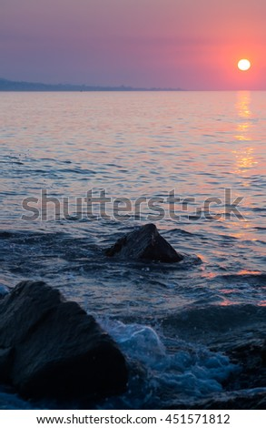 Dawn view of Mediterranean sea with sun and stones - stock photo