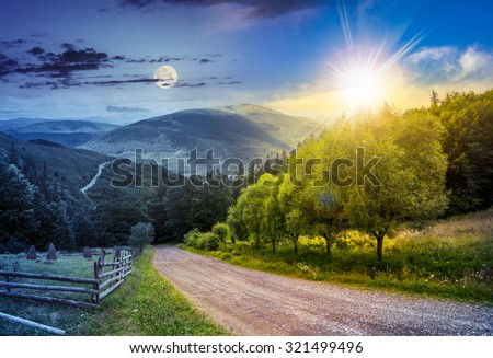day and night collage landscape. fence near road going down the hill through meadow and forest to the high mountains with sun and moon - stock photo