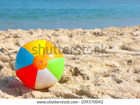 Day at the beach with a beach ball in the foreground. - stock photo