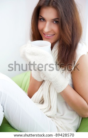 Day dreaming - Caucasian American female relaxed at home, having a cup of tea. Wearing wool scarf and gloves. Flu prophylaxis concept