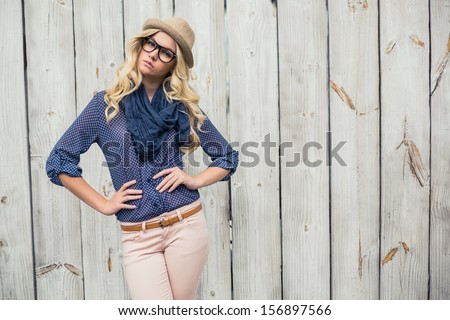 Day dreaming trendy blonde posing on wooden background - stock photo