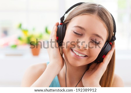 Day dreaming with her favorite music. Cheerful teenage girl in headphones listening to the music and keeping eyes closed while sitting in her apartment - stock photo