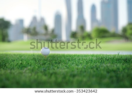 Day of golf. Golf ball is on the tee for a golf ball on the green grass of the golf course against the backdrop of the city skyline - stock photo