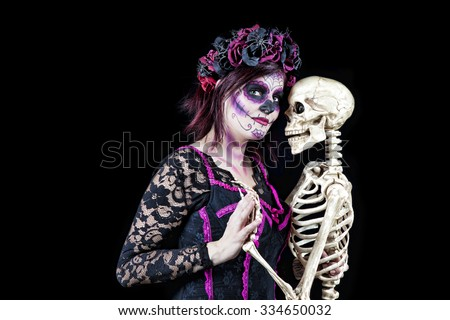 Day of The Dead. A woman dressed as a sugar skull dancing with the skeleton of a departed love one.
