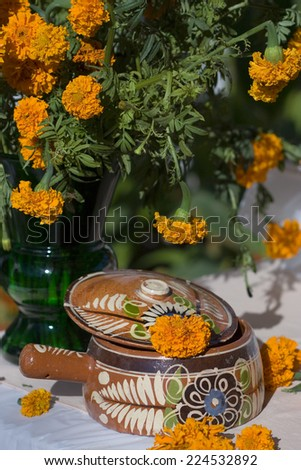 Day of the Dead celebration table with marigolds and food - stock photo