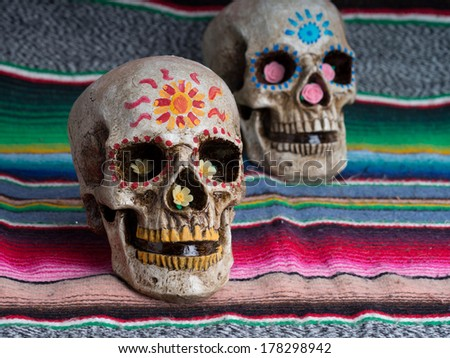 Day of the Dead (dia de los muertos) decorated skulls with colorful Mexican blanket - stock photo