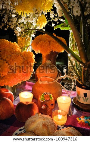 Day of the dead offering altar (Dia de Muertos) Celebration with bread ¨Pan de Muerto¨ chocolate skull and flowery in background. - stock photo