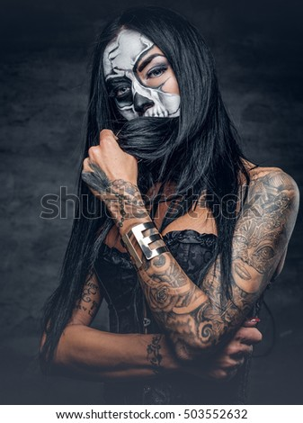 Day of the dead. Tattooed female with sugar skull make up.