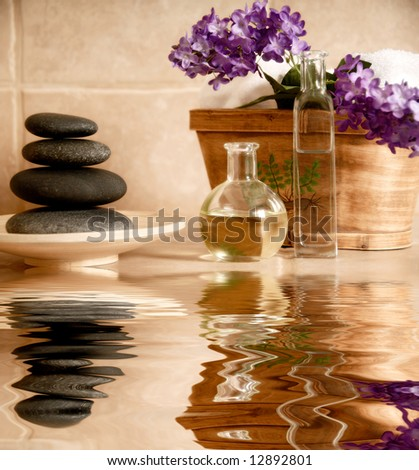 day spa products with stones, oil container, flowers - stock photo