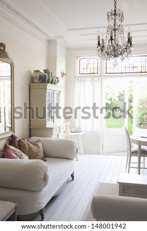 Daybed with cushions and glass chandelier in rustic home - stock photo