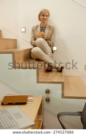 Daydreaming blonde woman sitting in stairway, looking away. - stock photo
