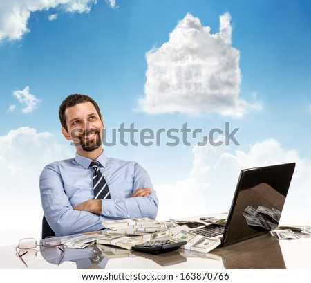 Daydreaming businessperson with arms crossed / happy guy smile day dreaming with his arms crossed sitting at his desk with laptop and a lot of money  - stock photo