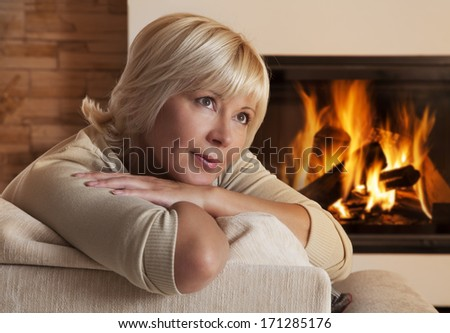 Daydreaming Caucasian woman sitting on sofa at home by fireplace