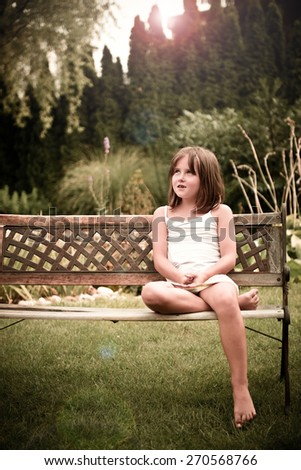 Daydreaming child portrait - little girl sitting on bench outdoor in backyard, lens flare visible - stock photo