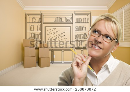 Daydreaming Woman Holding Pencil In Empty Rom with Built In Shelf Design Drawing on Wall. - stock photo